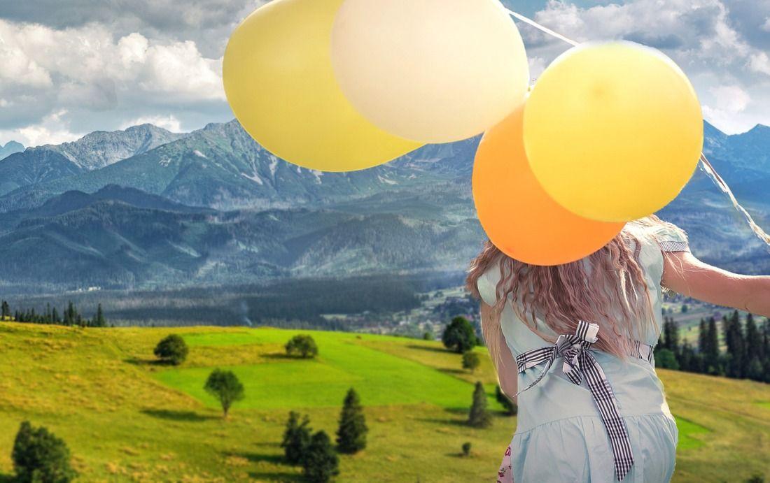góry i dziecko z balonami